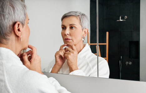 Senior woman spending time at home standing in bathroom looking in a mirror