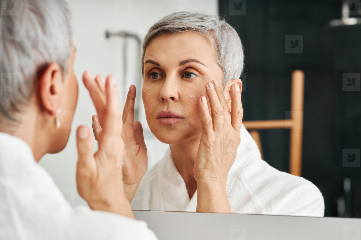 Senior woman applying moisturizer in the bathroom looking at her reflection