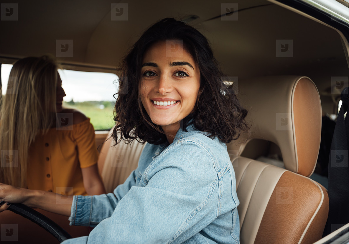 Smiling brunette woman on driver seat looking at camera