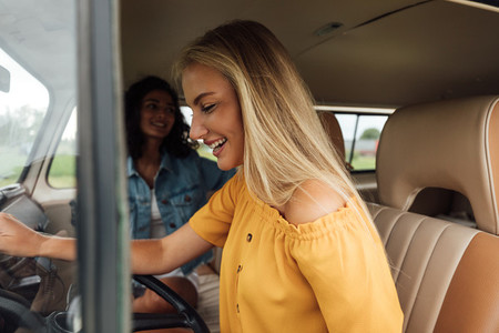 Side view of a blond woman on driver seat in a camper van