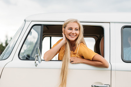 Happy woman with long hair looks out of car window while sitting on driver seat