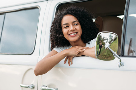 Young mixed race woman looking out of the car and smiling
