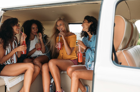 Beautiful young women sitting in van drinking cocktails and talking  Four people in a car during a road trip