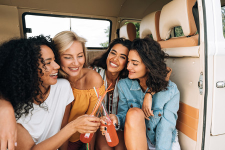 Two smiling women toasting with bottles in van  Close friends enjoying summer road trip
