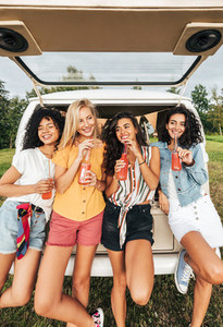 Group of diverse women holding cocktails while standing at the back of camper van  Four females with bottles standing at a car during summer vacation