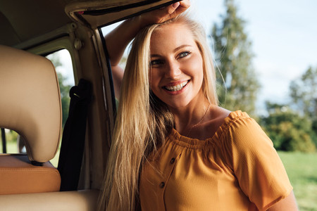 Beautiful blond woman in casual clothes leaning on camper van looking away
