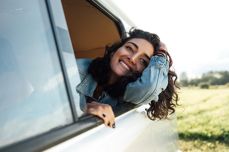 Attractive young woman enjoying road trip  Smiling female looks out of van window