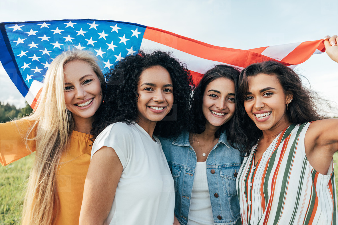 Group of young multi ethnic women holding American flag celebrating 4th of July