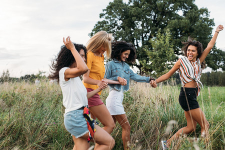 Laughing woman runs in front of her friends with a raised hand  Group of four young females on summer vacation