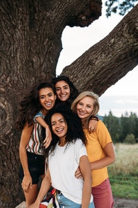 Group of young diverse women standing in front of a big tree and looking at camera