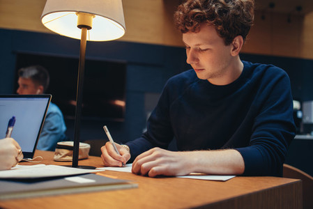 Young man studying in college library