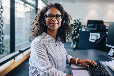 Confident female executive wearing headset