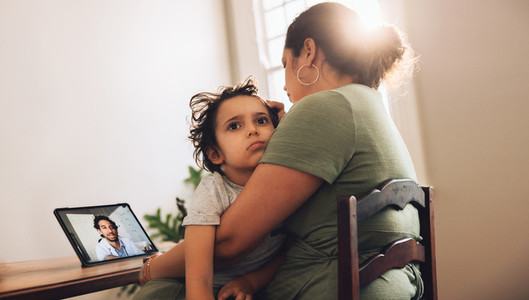 Mother and son having online medical consultation at home