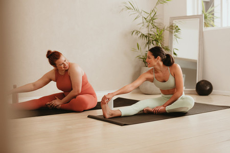 Two females exercising together in fitness studio