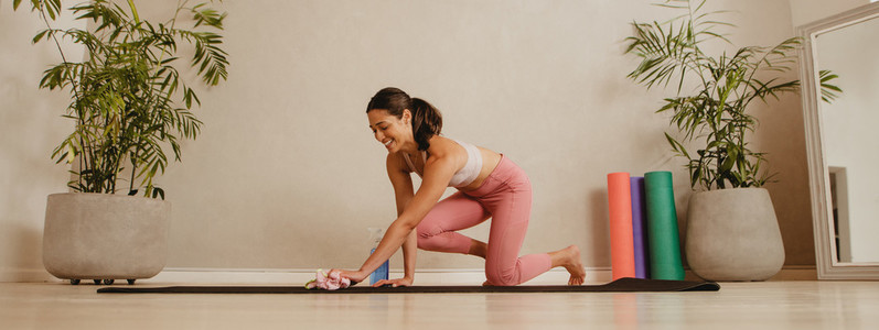 Woman disinfecting yoga mat after exercising