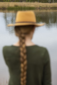 Woman with long braid in hat at lakeside