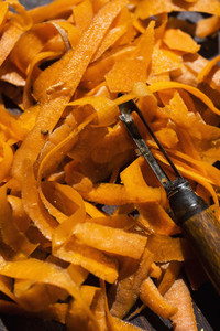Close up vibrant orange carrot strips and peeler