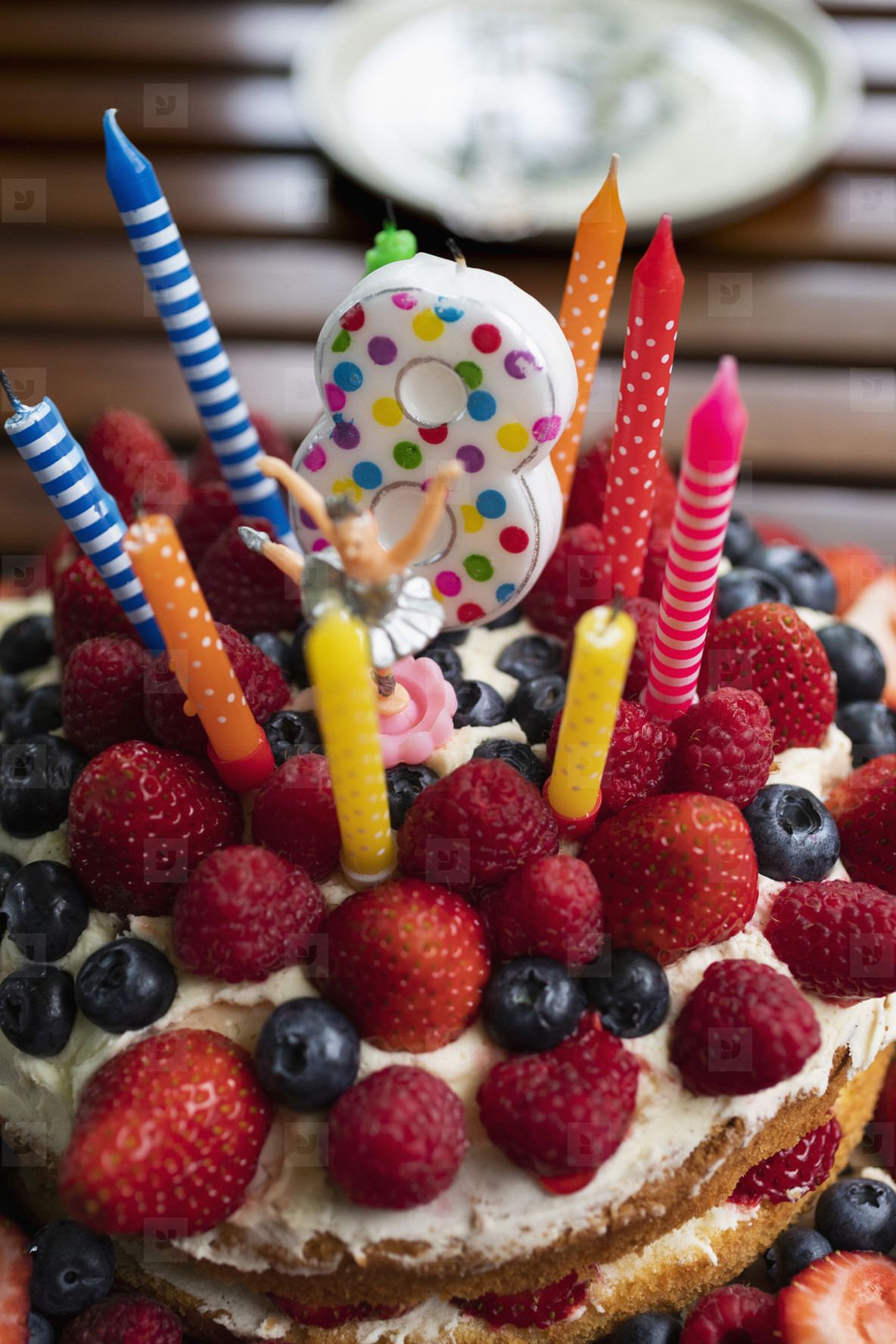 Vibrant candles and number 8 candle on fruit birthday cake