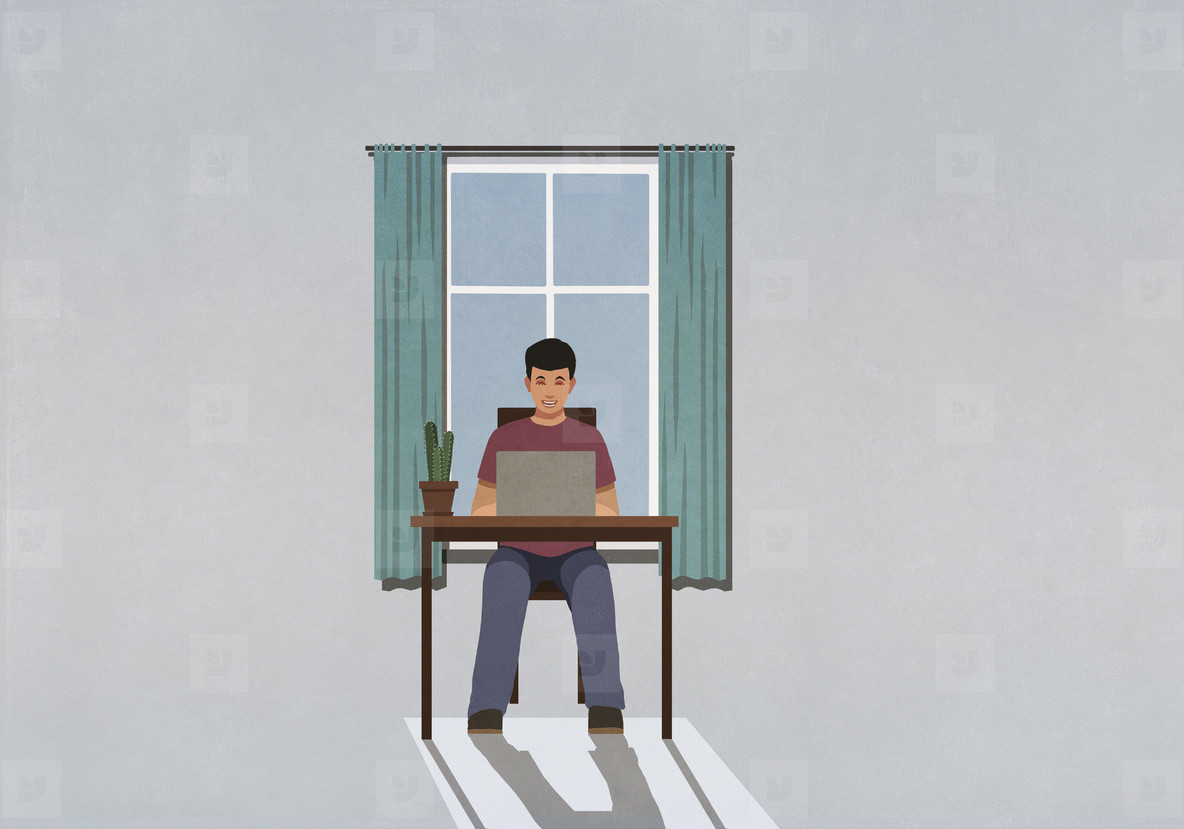 Man working from home at laptop in window