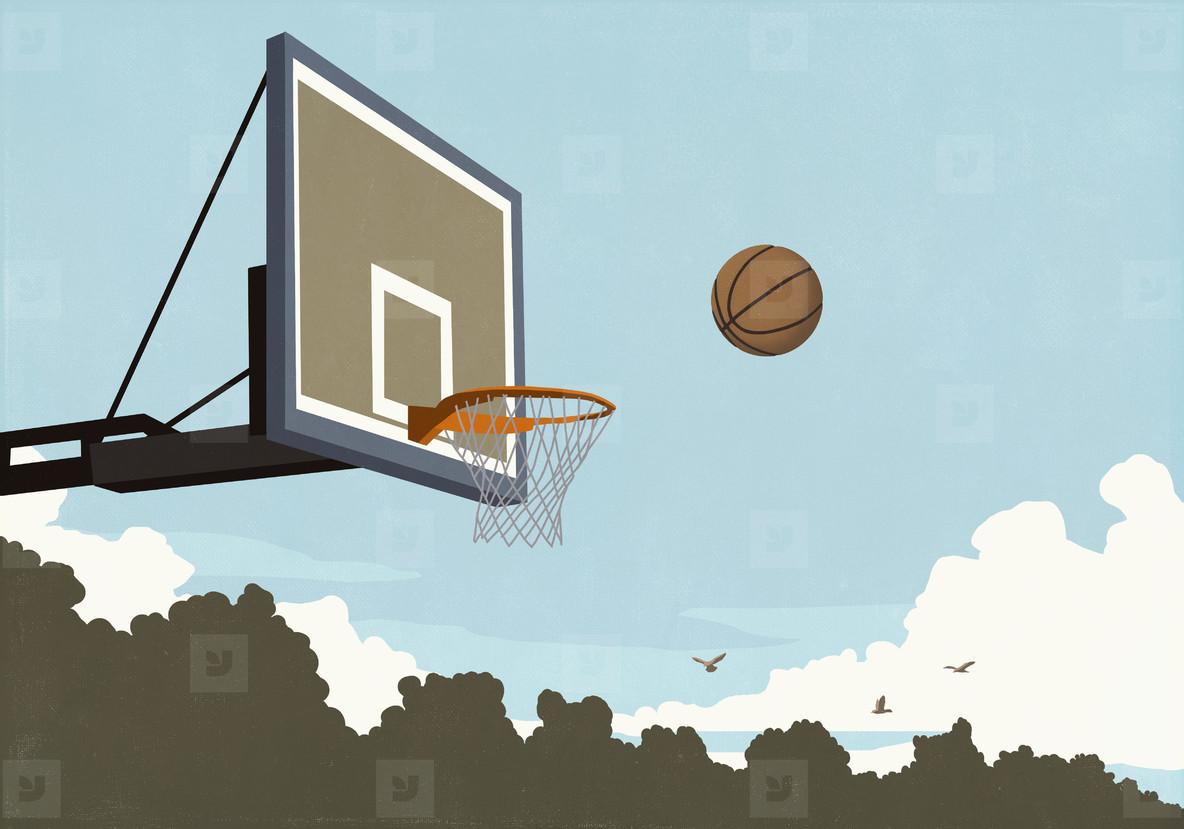 Basketball flying midair toward basketball net
