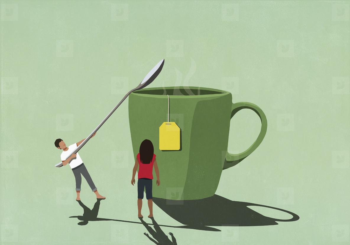 Couple with large spoon stirring sugar into mug of tea