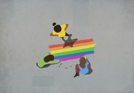 Women coloring rainbow with sidewalk chalk