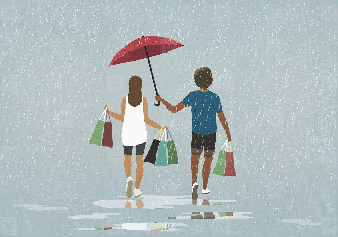Husband holding umbrella over wife with shopping bags in rain