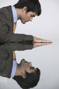 Reflection of businessman in conference room table
