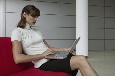 Businesswoman using laptop in office lobby