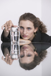 Businesswoman looking at water glass on conference table