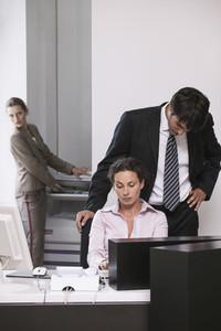 Businessman looking over shoulder of businesswoman in office