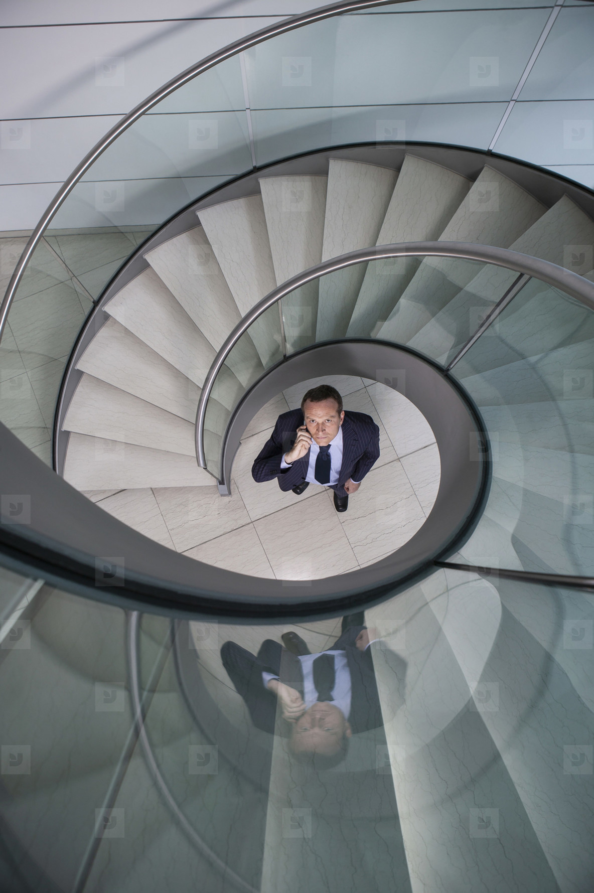 Portrait businessman talking on smart phone below spiral staircase