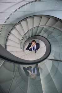 Portrait businessman talking on smart phone below spiral staircase