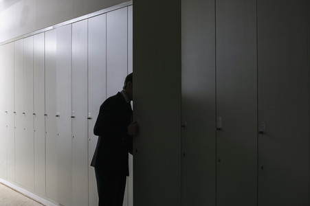 Businessman peering into locker