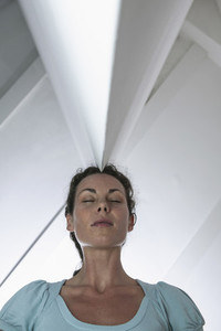 Serene businesswoman standing below angled ceiling