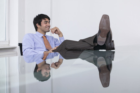 Carefree businessman with feet up in conference room meeting