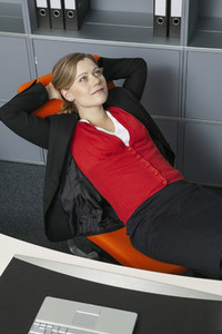 Carefree businesswoman relaxing with hands behind head in office