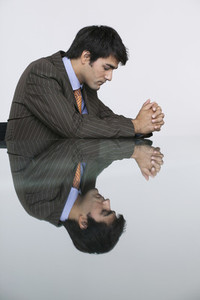 Reflection of thoughtful businessman in conference room table