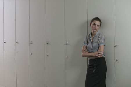 Portrait serious young businesswoman at lockers