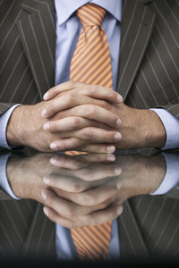 Close up businessman with hands clasped on reflective table