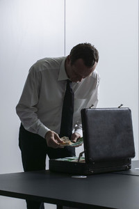 Businessman counting money at briefcase in office