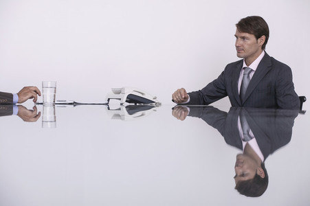 Reflection of businessman in conference room meeting table