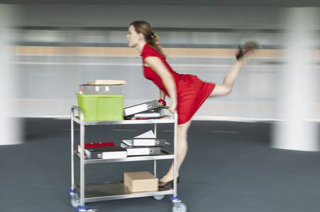 Carefree businesswoman pushing and riding office cart