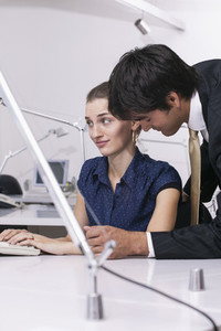 Businessman flirting with disgusted businesswoman in office