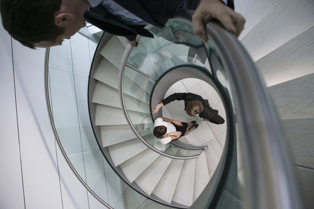 Businessman watching colleagues talk at bottom of spiral staircase