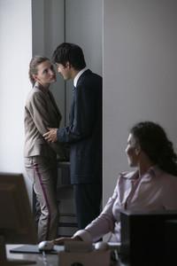 Businessman cornering businesswoman at photocopier in office