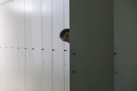 Portrait playful businessman peering from inside locker