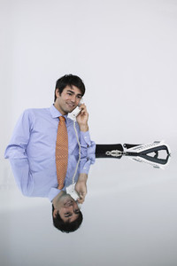 Smiling businessman talking on conference telephone in conference room