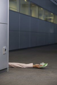 Arm of businesswoman holding cash on office floor