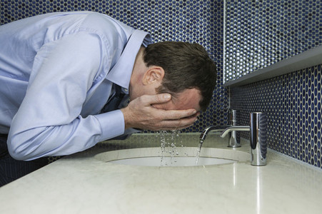 Businessman splashing water on face at bathroom sink